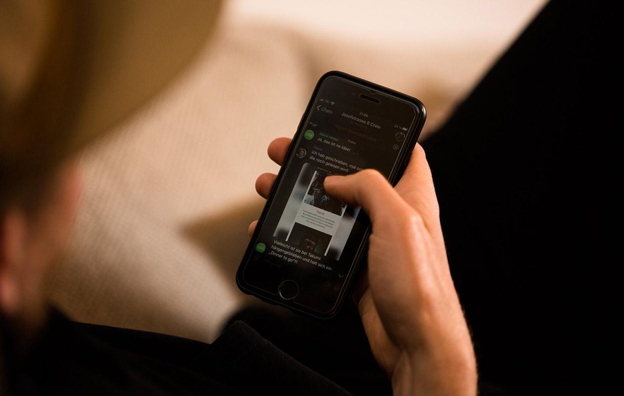 Hände mit einem Smartphone in der Hand.
