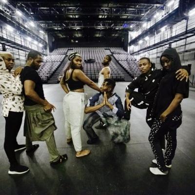 Tänzer*innen auf einer Bühnen posieren für ein Foto.