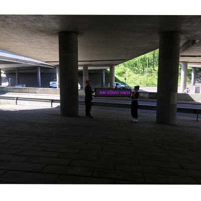 """Unter einer Autobahnbrücke stehen zwei Menschen und halten ein LED Panel hoch, das aus dem Schatte heraus grell pink die Worte """"IHR KÖNNT MICH"""" aussendet."""
