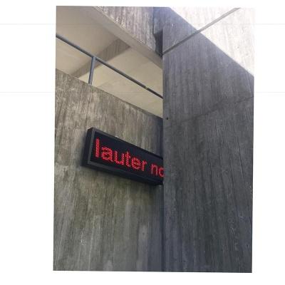 """Zwischen grauen Betonwänden schaut ein LED-Leuchtpanel hervor, auf dem in roten Buchstaben """"lauter no-"""" steht."""
