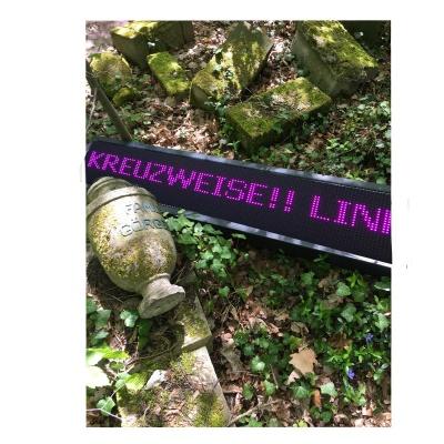 """Ein LED-Leuchtpanel liegt zwischen alten umgestoßenen Urnen und Grabsteinen auf dem Waldboden. In grell pinken Buchstaben laufen die Worte """"KREUZWEISE!! LINK"""" darüber."""